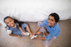 Portrait of mother helping daughter to wear shoe at home stock images