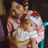 A portrait of a mother with her baby boy who is 3 months old in the mother`s arms. Babies pose using Balinese headbands and red stock images