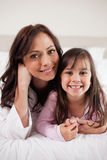Portrait of a mother and her daughter lying on a bed Stock Photos