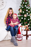 Portrait of mother and her daughter sitting in decorated living. Portrait of young mother and her daughter sitting in decorated living room with Christmas tree Stock Photography