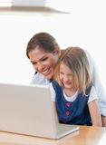 Portrait of a mother and her daughter using a notebook Stock Images