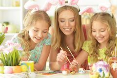 Portrait of mother with her daughters preparing for Easter stock image