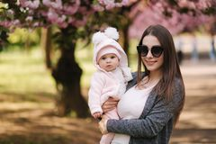 Portrait of mother and her little baby girl. Beautiful mom and cute baby. Mother hud her daughter. Baby dressed in stock image