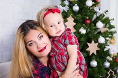 Portrait of mother and her little daughter with Christmas tree Royalty Free Stock Photography
