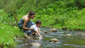 Portrait of Mother with her son are launching the toy paper boat on a stream stock video footage