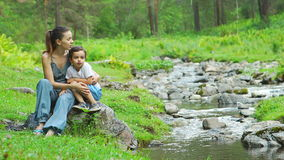 Portrait of mother with her son near a stream stock video