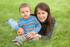 Portrait of a mother and her son outdoors. A mother and her son holding an apple are resting on the summer meadow Royalty Free Stock Images