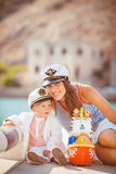 Portrait of a mother with her son playing on the jetty by the sea in the city, still life photo. Mother and baby son playing toys near the sea Royalty Free Stock Images