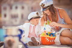 Portrait of a mother with her son playing on the jetty by the sea in the city, still life photo. Mother and baby son playing toys near the sea Stock Images