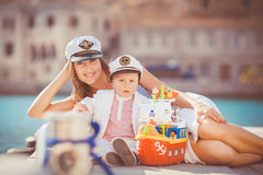 Portrait of a mother with her son playing on the jetty by the sea in the city, still life photo. Mother and baby son playing toys near the sea Royalty Free Stock Image