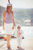 Portrait of a mother with her son playing on the jetty by the sea in the city, still life photo. Mother and baby son playing toys near the sea Stock Image