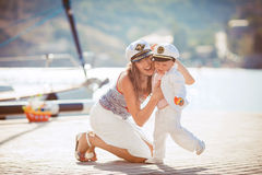 Portrait of a mother with her son playing on the jetty by the sea in the city, still life photo. Mother and baby son playing toys near the sea Stock Photography