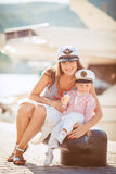 Portrait of a mother with her son playing on the jetty by the sea in the city, still life photo. Mother and baby son playing toys near the sea Royalty Free Stock Photography