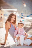 Portrait of a mother with her son playing on the jetty by the sea in the city, still life photo. Mother and baby son playing toys near the sea Royalty Free Stock Photos
