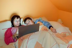Portrait of a mother and her son using laptop Stock Image