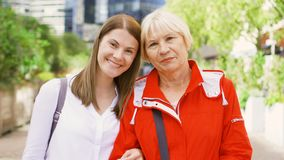 Portrait of mother and her young daughter standing on street. Happy family enjoying time together stock footage
