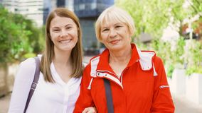 Portrait of mother and her young daughter standing on street. Happy family enjoying time together stock video footage