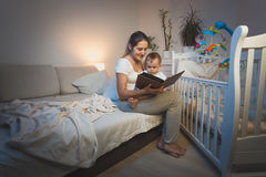 Portrait of mother holding baby boy on knees and reading him a b Stock Photo
