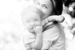 Portrait of a mother holding  child on  sunny day. Black and white Royalty Free Stock Photo