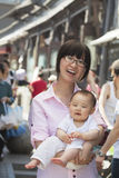 Portrait of mother holding her baby son, outdoors Beijing Stock Image
