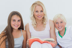 Portrait of mother holding a storybook to her children Royalty Free Stock Image