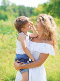 Portrait of mother hugging child son outdoors in summer Royalty Free Stock Image