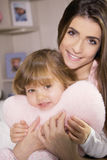 Portrait of mother hugging little daughter smiling looking camera Royalty Free Stock Images