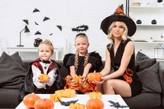 portrait of mother and kids in halloween costumes with pumpkins in hands sitting on sofa stock photography