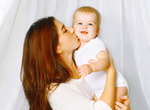 Portrait mother kissing baby on the bed home Stock Image