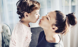 Portrait of a mother kissing her beloved child Stock Images