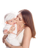 Portrait of a mother kissing her daughter. Stock Images