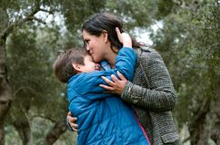 Portrait of a mother kissing her little son in the park royalty free stock photography