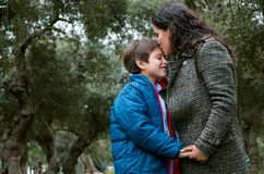 Portrait of a mother kissing her little son in the park stock photo