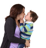 Portrait of a mother kissing her son. Portrait of a mother kissing her little boy isolated on a white background Royalty Free Stock Photo