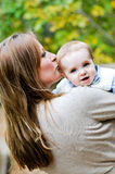 Portrait of mother kissing infant son outdoors Royalty Free Stock Image