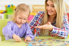 Portrait of mother with little daughter collecting puzzle. Mother with little daughter collecting puzzle at home stock photos