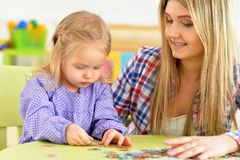 Portrait of mother with little daughter collecting puzzle. Mother with little daughter collecting puzzle at home stock image