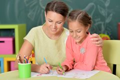 Portrait of mother with little daughter drawing with colorful pencils royalty free stock photography