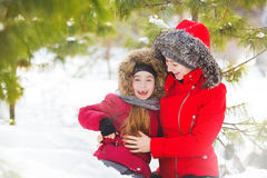 Portrait of mother and little daughter smile in snow in winter wood Stock Images