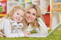 Portrait of mother with little daughter using laptop while lying on floor royalty free stock photo