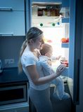 Portrait of young mother looking for food in refrigerator at night to feed her little baby boy Royalty Free Stock Photo