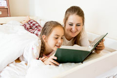 Portrait of mother lying with daughter on bed and reading book Royalty Free Stock Photography