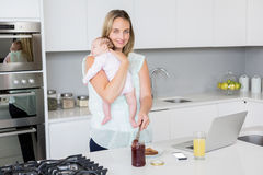 Portrait of mother putting jam on bread while carrying her baby Stock Photos