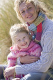 Portrait of mother sitting with daughter on beach Stock Photography