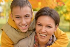 Close up portrait of mother with son in autumnal park royalty free stock photo