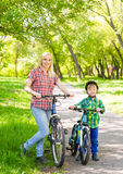 Portrait of mother and son on the bikes in the park.  Royalty Free Stock Photo