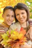 Portrait of a mother with son portrait. Close up portrait of mother with son hugging outoors in autumnal park stock photo
