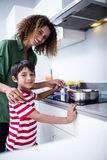 Portrait of mother and son cooking in kitchen. At home Stock Photo