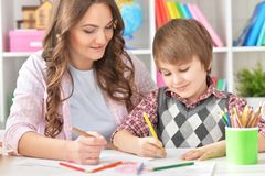 Portrait of Mother and son drawing at home. Mather and her little son drawing with colorful pencils Stock Photos