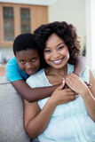 Portrait of mother and son embracing each other in living room. At home stock image